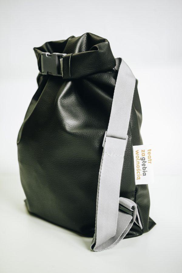 Czarny plecak w kształcie worka.. Wykonany ze sztucznej skóry. Z szarymi ramiączkami.
