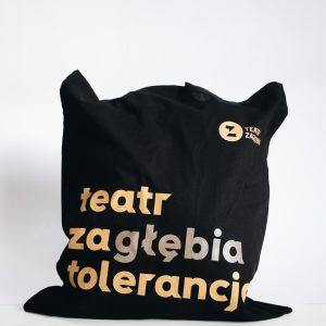 Czarna torba na ramię. Nadrukowany pomarańczowy napis teatr zagłębia tolerancją.