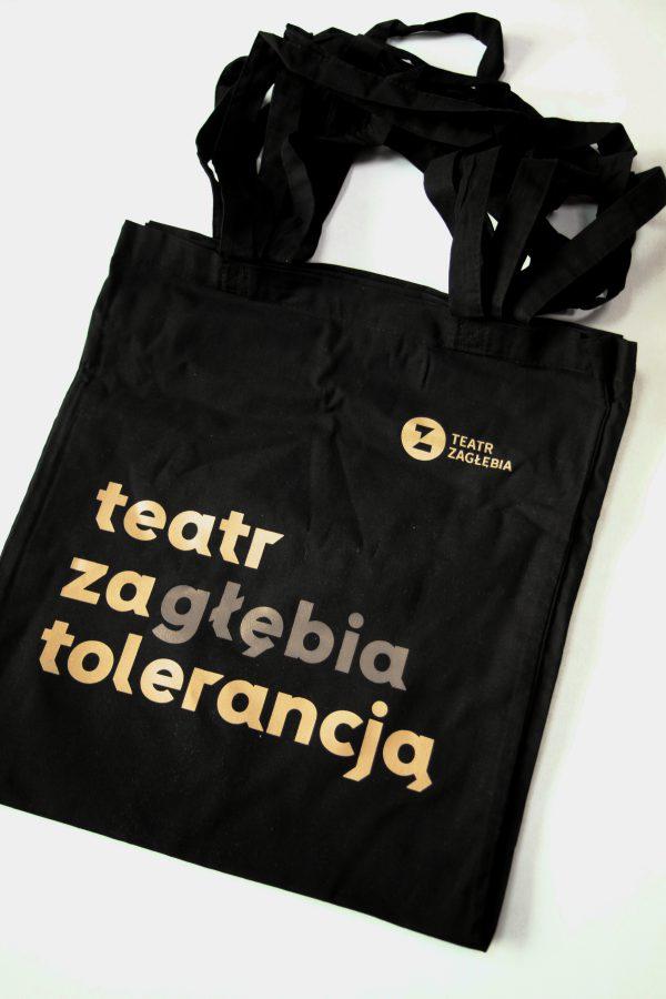 Czarne torby na ramię z logiem Teatru Zagłębia w prawym, górnym rogu i pomarańczowym napisem teatr zagłębia tolerancją.