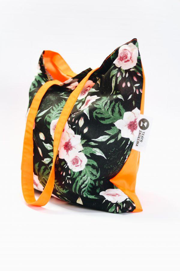 Pomarańczowa torba na ramię. Po prawej stronie metka z logo Teatru. Front torby z kwiecistego materiału.