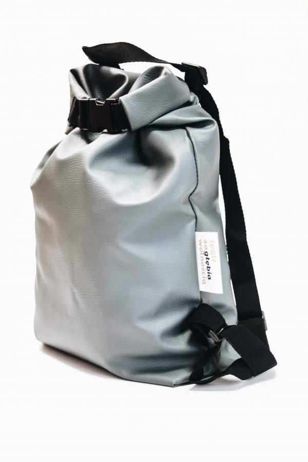 Szary plecak wykonany ze sztucznej skóry. Ma kształt worka. Ma czarne ramiączka.